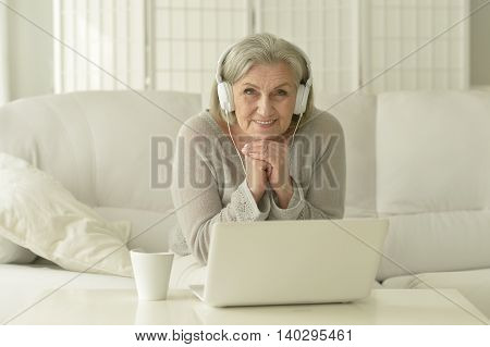 happy Elderly woman with laptop and coffee at home