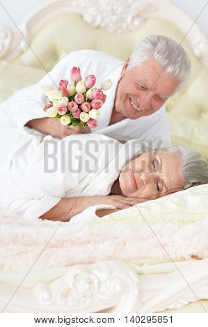 happy senior man gives flowers to a woman