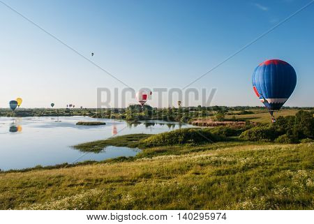 colorful balloons flying over the lake and field