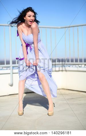 Pretty girl in dress stands on roof of tall building and shouts on wind at sunny day