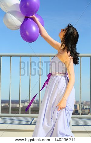 Girl brunette in blue dress holds white and purple air balloons on roof