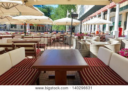 empty street cafe interior in city, tables and chairs under umbrella, summer season, no people