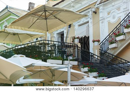 empty street cafe interior in city with stairs, tables and chairs, ornate with flowers, summer season, no people