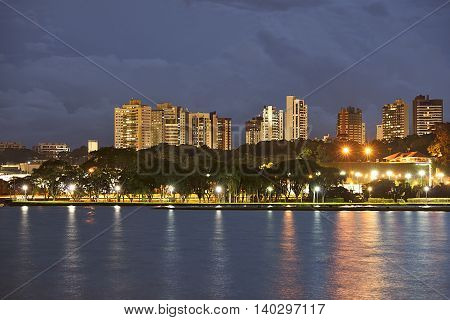 night photography of urban park with lake and building in the background