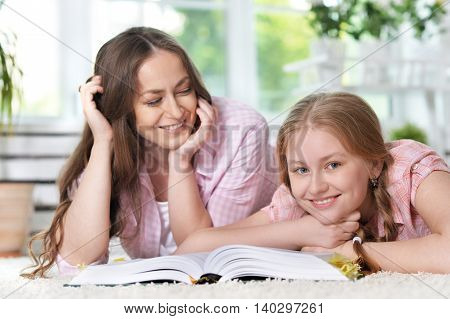 portrait of mother helping her  daughter with homework