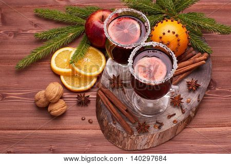 Mulled wine, fir branches, spices, fresh orange and apple on wooden table