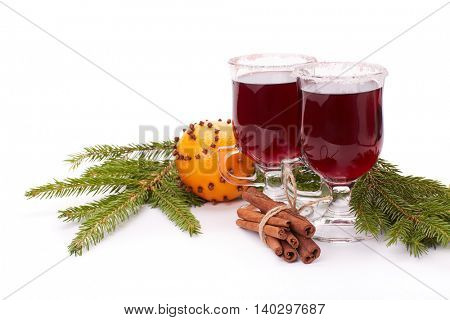 Two glasses with mulled wine, fir branches, sticks of cinnamon and fresh orange on a white background