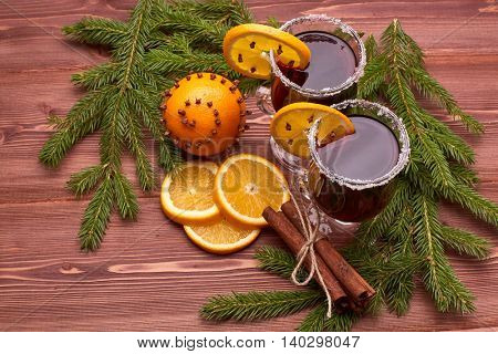 Mulled wine, fir branches, fresh orange and spices on wooden table