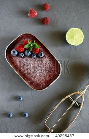 Raspberry and blueberry homemade ice cream in a metal bowl, decorated with raspberries, blueberries, mint and Ice-cream scoop, raspberries, blueberries and lime on a gray background, flat lay