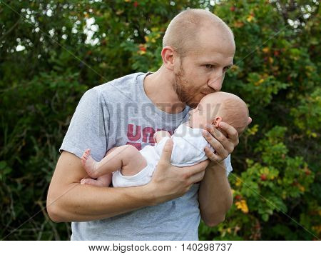 Father kissing the baby in the forehead in the park against green bushes