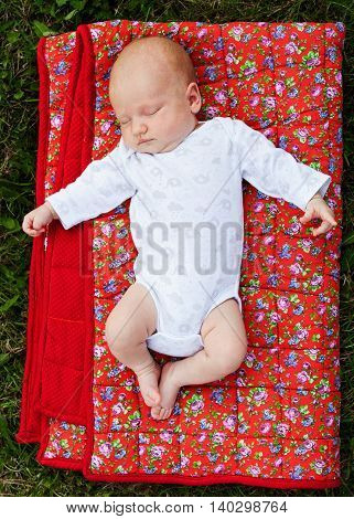 Newborn baby sleeping on a red blanket outdoors
