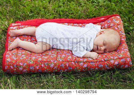 Happy newborn baby sleeping on a red blanket on green grass