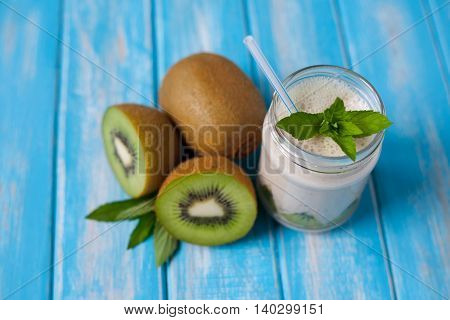 Kiwi and banana smoothie and freshly cut half and whole kiwi with mint on rustic blue background, view from top, horizontal
