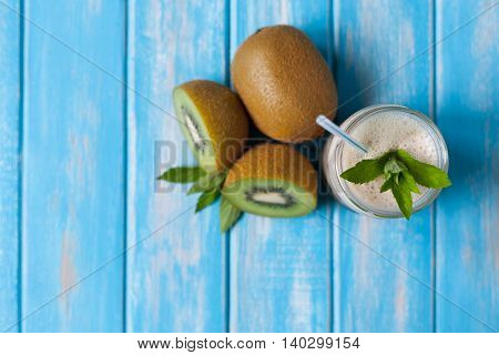 Kiwi and banana smoothie and freshly cut half and whole kiwi with mint on rustic blue background, flat lay, horizontal