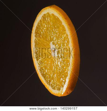 Orange slice on a dark background. Studio photo