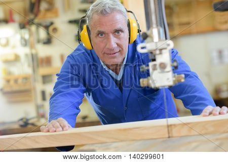senior carpenter cutting wood with bandsaw in workshop