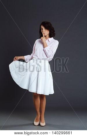 Beautiful young woman posing over grey background and make silence gesture
