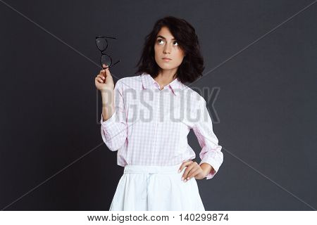 Beautiful young woman holding glasses in hand posing over grey background