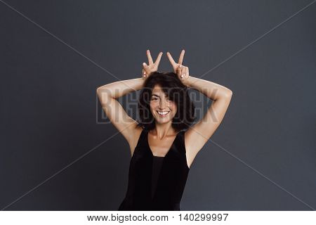 Beautiful young woman posing over grey background and make funny gesture