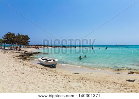 Elafonisi, Island Crete, Greece, - June 26, 2016: The lagoon of beautiful beach of Elafonisi with pink sand, boat and peopleMediterranean Sea)