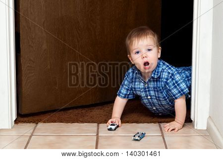 A baby boy crawls through a doorway while playing cars. He has a police car in hand and a blue car lays upside down ahead of him. He looks shocked and amazed with an open mouth and big eyes.
