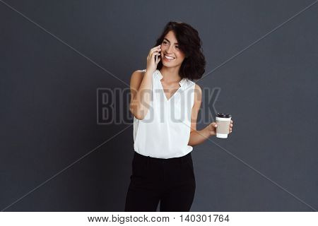 Cheerful young woman talking on her phone and holding coffee in hand over grey background