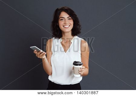 Cheerful young woman holding her phone and coffee in hands over grey background