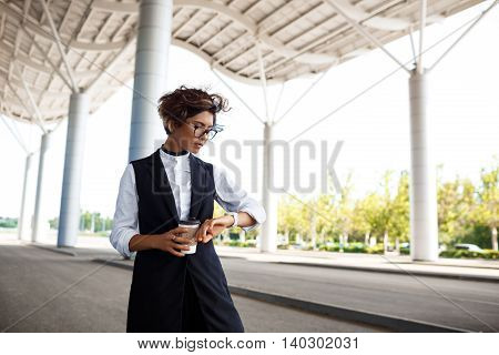 Young successful businesswoman in glasses looking at watch, holding coffee, standing near business centre.