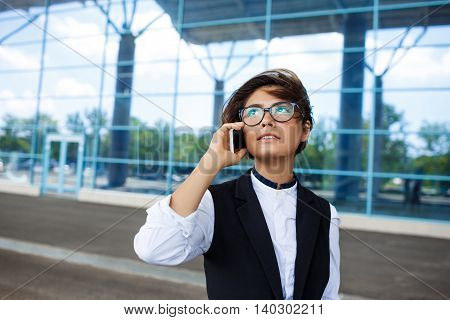 Young successful businesswoman in glasses speaking on phone, smiling, standing near business centre.