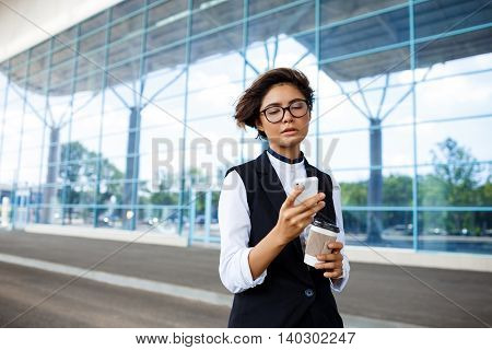 Young successful businesswoman in glasses looking at phone, holding coffee, standing near business centre.