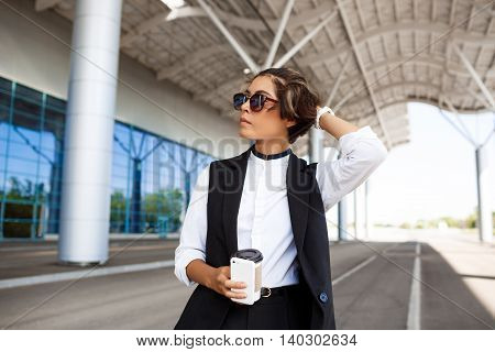 Young successful businesswoman in sunglasses holding coffee and phone, standing near business centre.