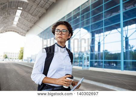 Young successful businesswoman in glasses holding coffee and tablet, standing near business centre.