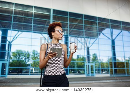 Young successful african businesswoman in glasses holding tablet and coffee, standing near business centre.
