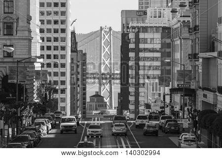 San Francisco, California, USA - January 14, 2013:  Black and white view of California Street with Bay Bridge background.