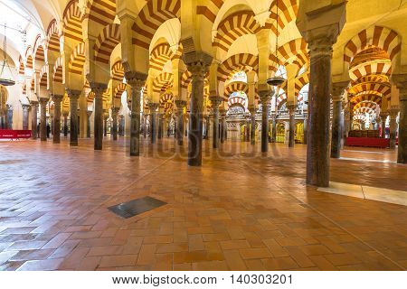 Cordoba, Andalusia, Spain - April 20, 2016: the popular arcades of Mezquita of Cordoba, a Roman Catholic cathedral and former mosque situated in the Andalusian city.