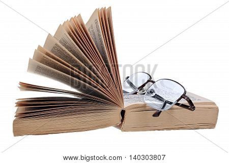 Open paperback and glasses isolated on white background with clipping path