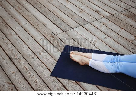 Close up photo of girl's legs in sport suit over wood background.