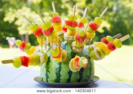 Watermelon decorated with colorful fruit skewers with shallow depth of field.