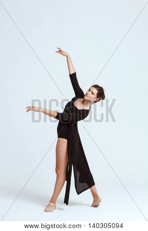 Young beautiful contemporary brunette dancer smiling, looking at camera, posing over white background. Copy space.