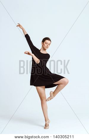 Young beautiful contemporary brunette dancer posing over white background. Copy space.