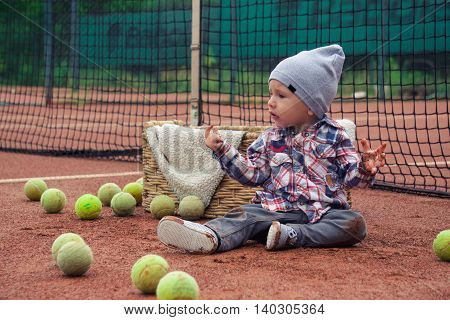 The little boy next to the basket. The little boy on the tennis court. Little boy and tennis balls