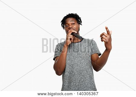 Young handsome african man singing in microphone over white background. Copy space.