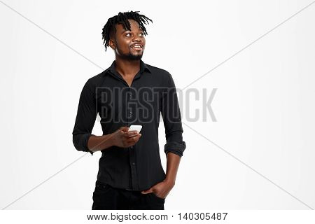 Young successful african businessman in black shirt smiling, posing, holding phone over white background. Copy space.