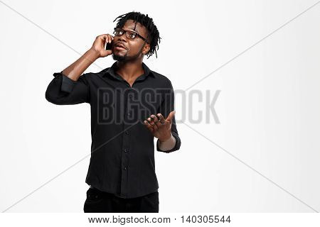 Young successful african businessman in black shirt and glasses speaking on phone, smiling over white background. Copy space.