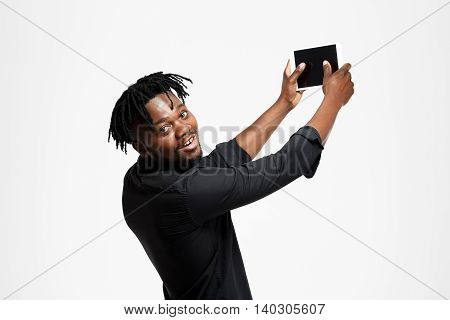 Young successful african businessman in black shirt making selfie, smiling, looking at camera over white background. Copy space.