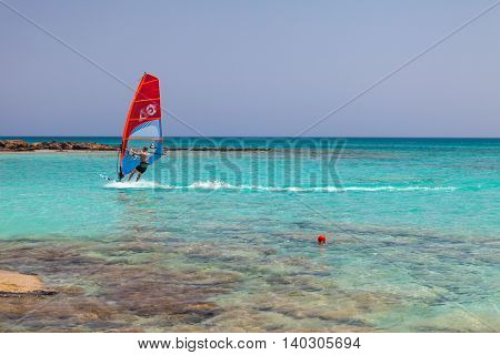 Elafonisi, Island Crete, Greece, - June 26, 2016: The windsurfer is moving in the Libyan Sea ( part of the Mediterranean Sea) on the beautiful beach of Elafonisi with pink sand.