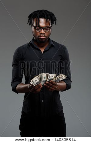 Young successful african businessman in black shirt and glasses holding money over dark background.