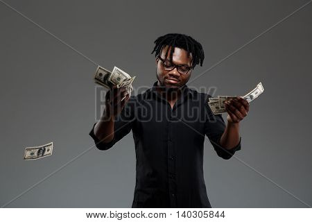 Young successful african businessman in black shirt and glasses throwing money over dark background. Copy space.