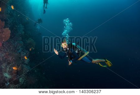 Scuba diver showing ok sign near coral reef in a tropical sea