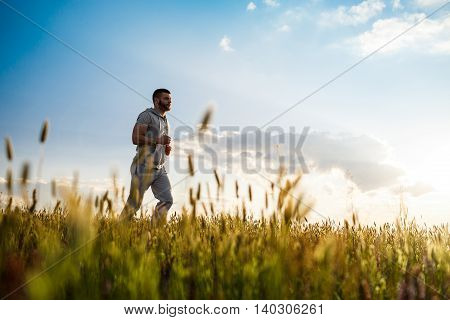 Young handsome sportive man jogging in field at sunrise.